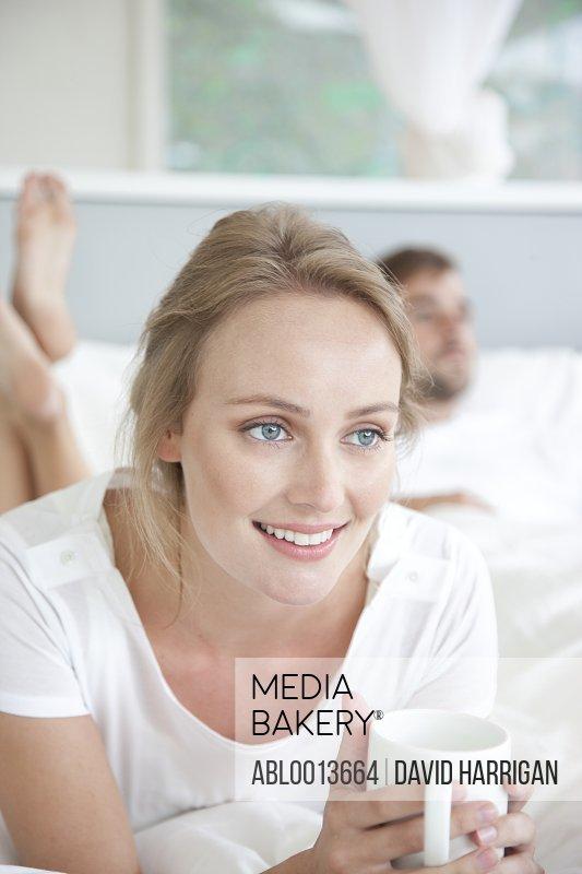 Woman Lying on Bed Holding Mug
