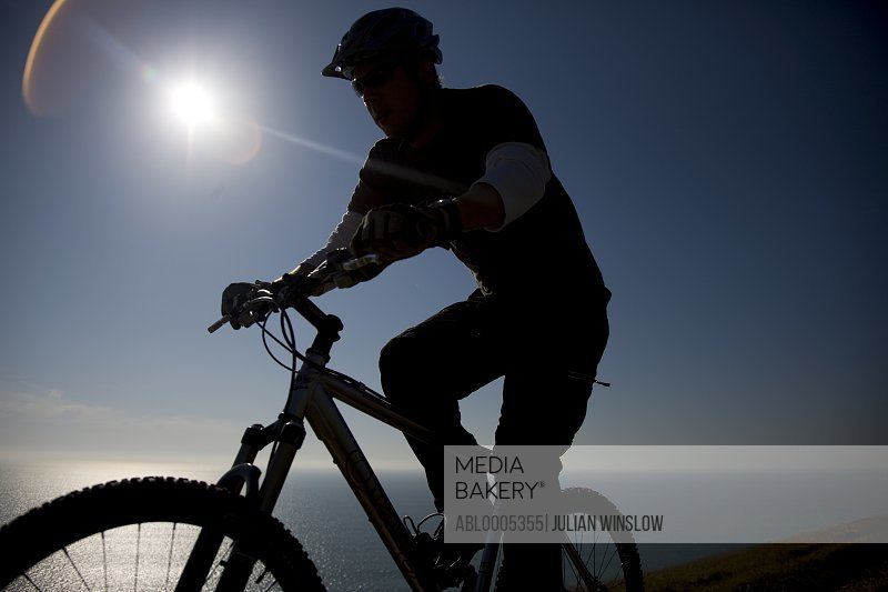 Man cycling by the ocean