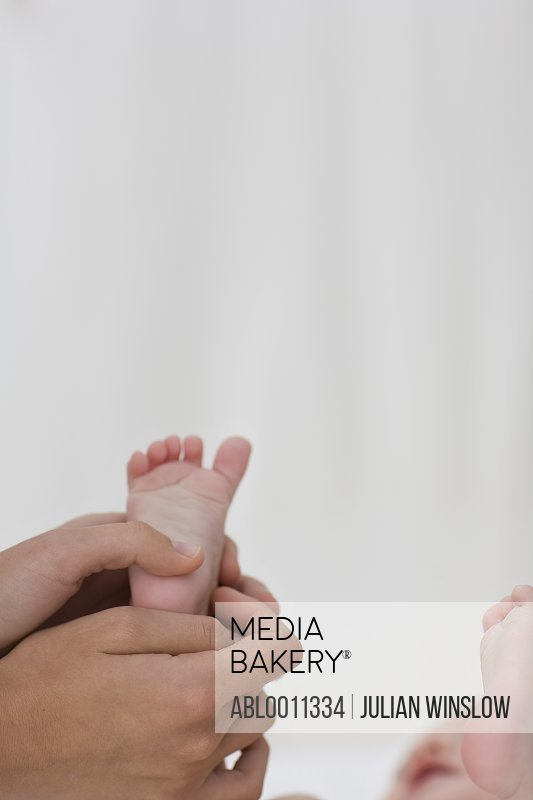 Close  up of woman's hand holding baby's foot
