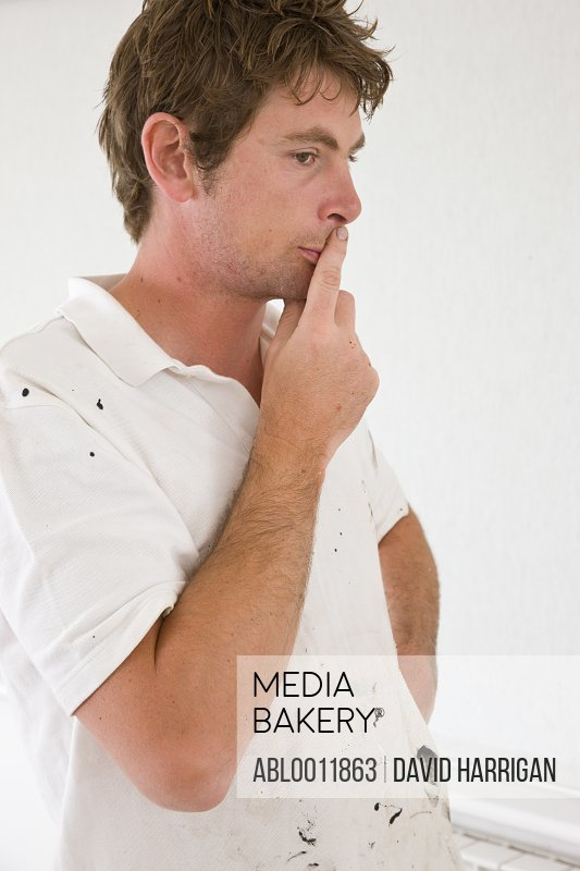 Close up of man standing with finger on lips thinking