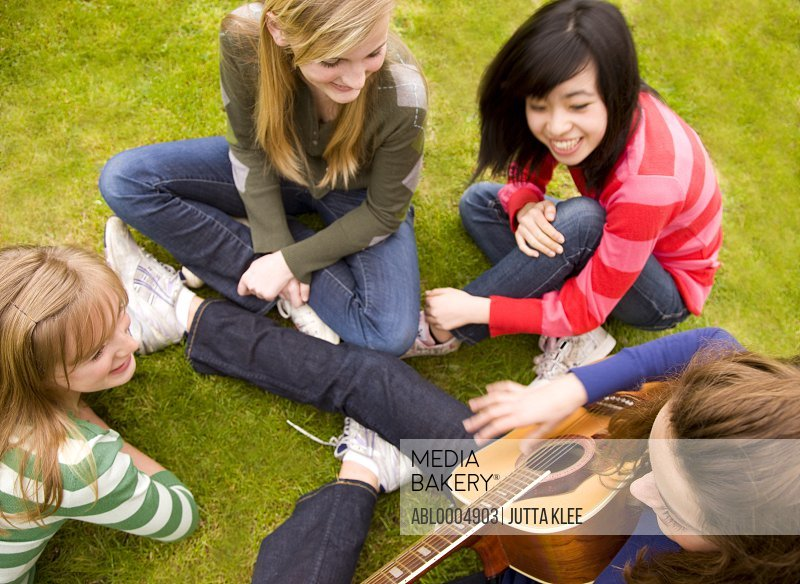 Teenage girls sitting in a garden singing and smiling with one of them playing the guitar