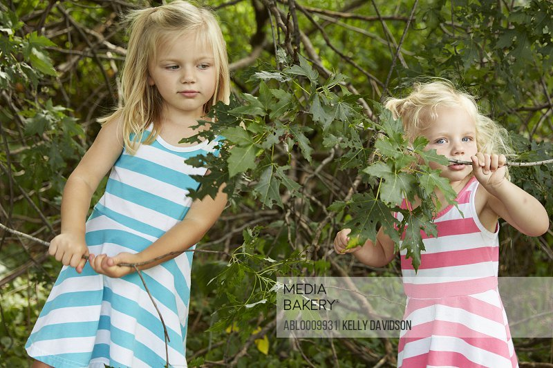 Two Young Girls Playing in Garden Holding Twigs with Leaves
