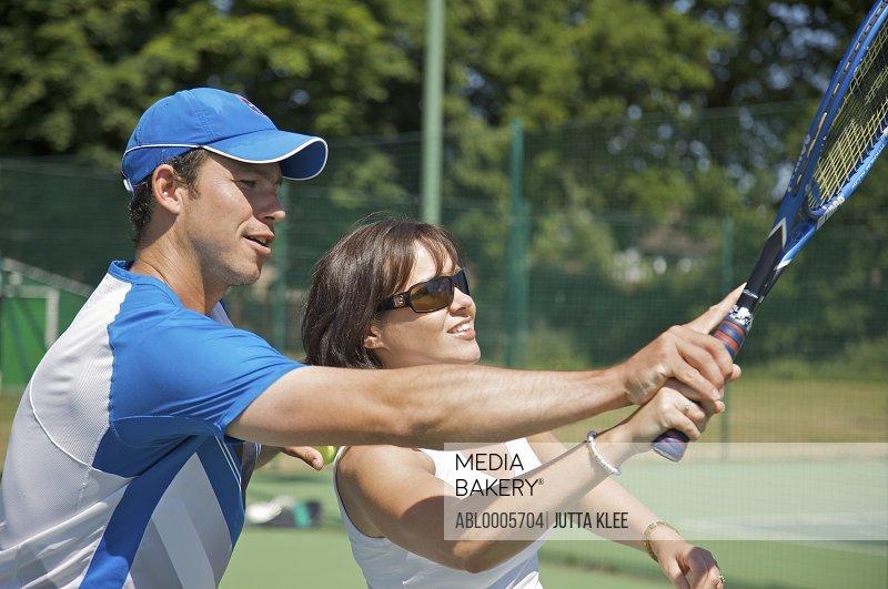 Tennis teacher instructing a woman