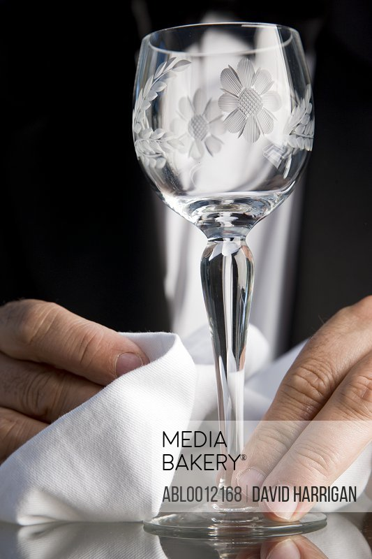 Close up of a waiter hands polishing a crystal glass