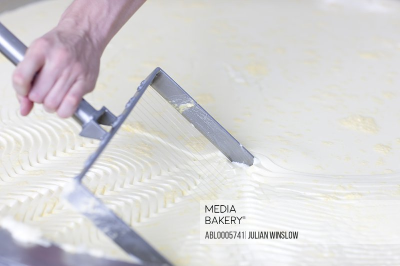 Close up of a man's hand cutting the curd