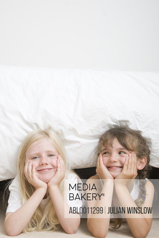 Two young girls with chin resting on hands under bed smiling