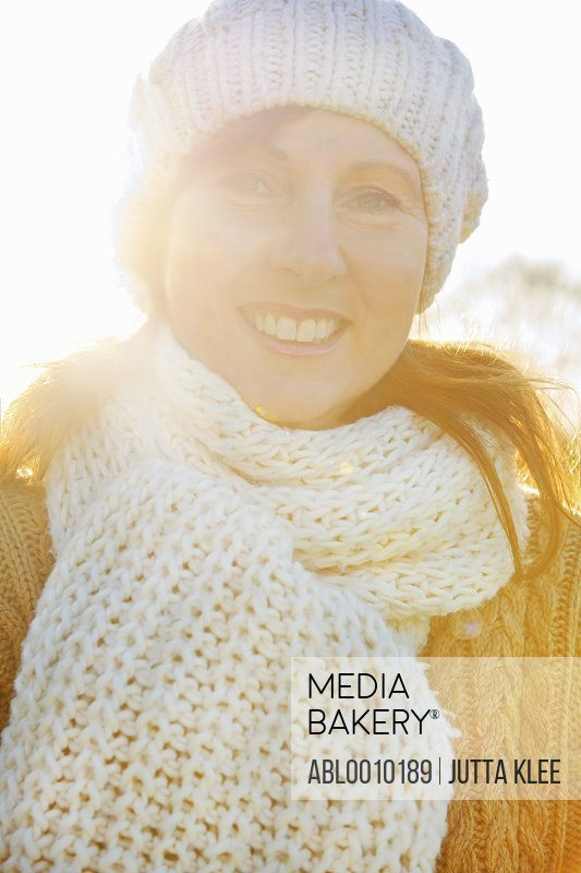 Woman Wearing Wool Hat and Scarf Smiling Outdoors