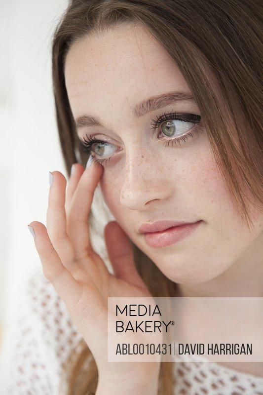 Teenage Girl Touching Corner of her Eye
