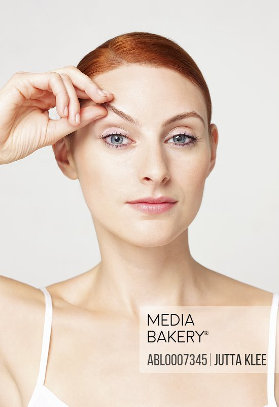 Woman Lifting Eyebrow with her Hand