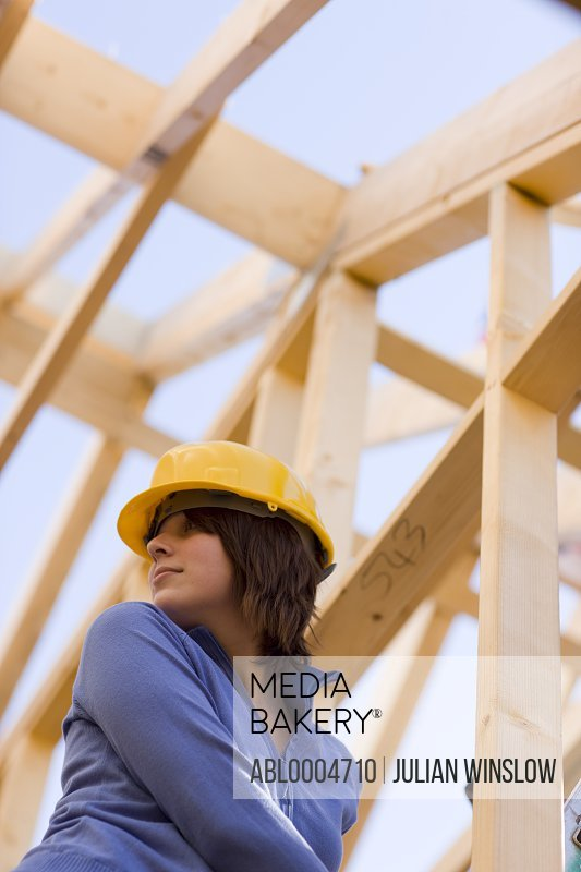 Young woman wearing hard hat at construction site looking behind  her shoulder