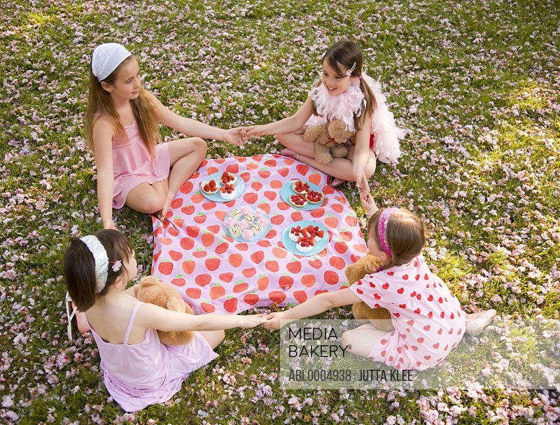 Four young girl sitting around a colorful blanket holding hands