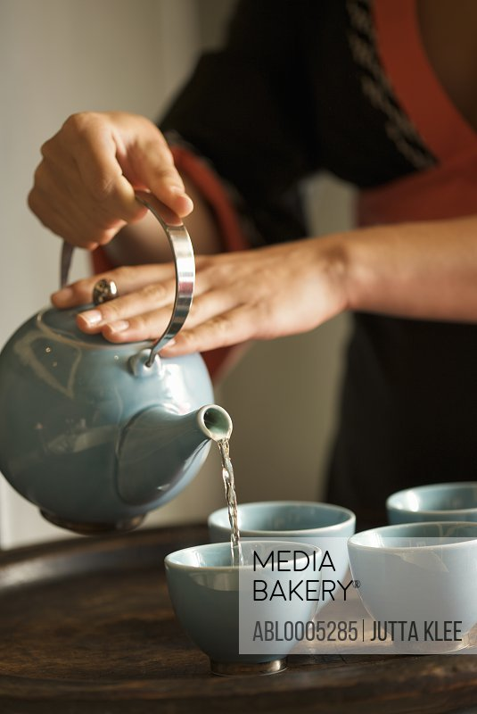 Close up of a woman hands pouring green tea