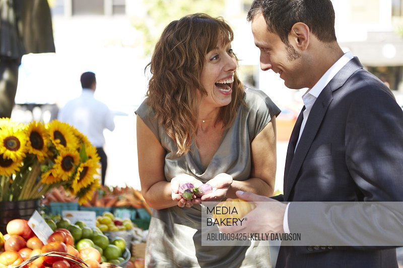 Smiling Couple at Farmers Market Holding Vegetables