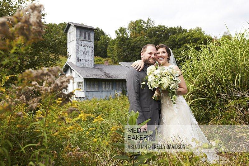 Bride and Groom Embracing in Meadow