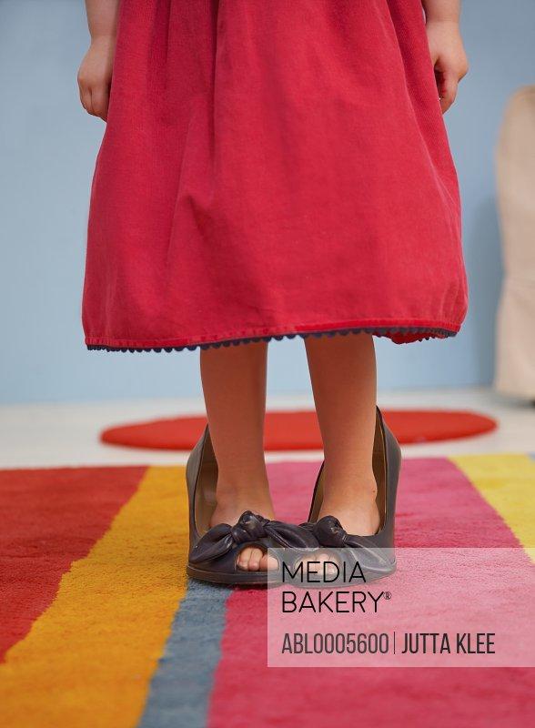 Young girl wearing woman shoes