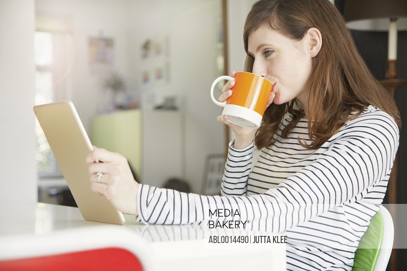 Woman Drinking Coffee and Using Digital Tablet at Home