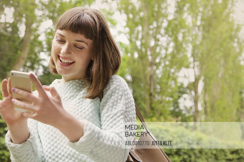 Teenage Girl Using Smartphone Outdoors, Smiling