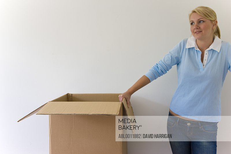 Young woman standing against white wall with one arm resting on a cardboard box