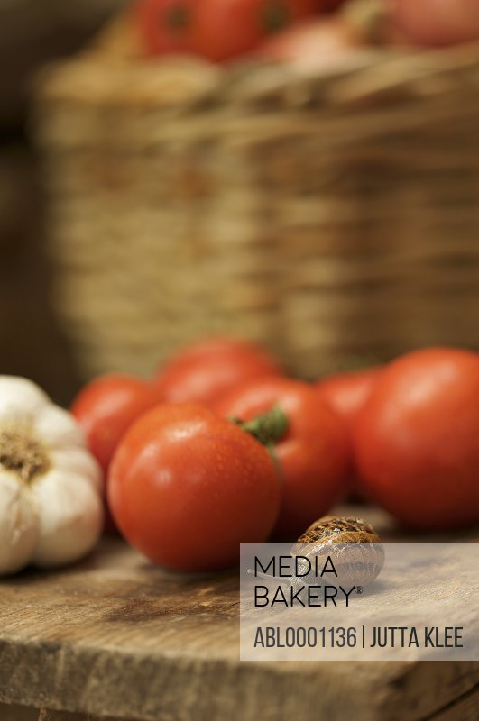 Close up of a snail slithering on a wooden bench next to few tomatoes and a garlic bulb