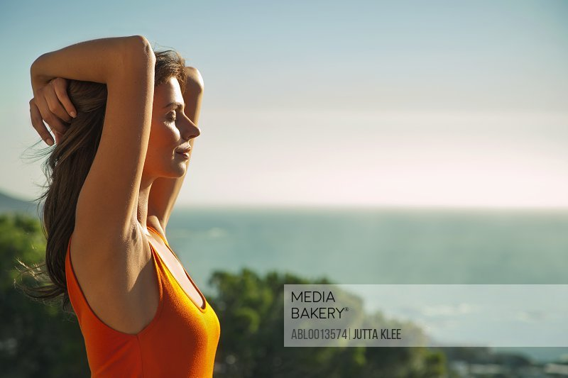 Profile of Woman with Arms Behind Head, Ocean in the background