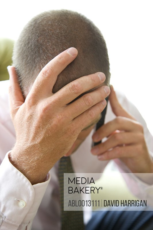 Close up of Businessman with Head in Hands Using Cell Phone