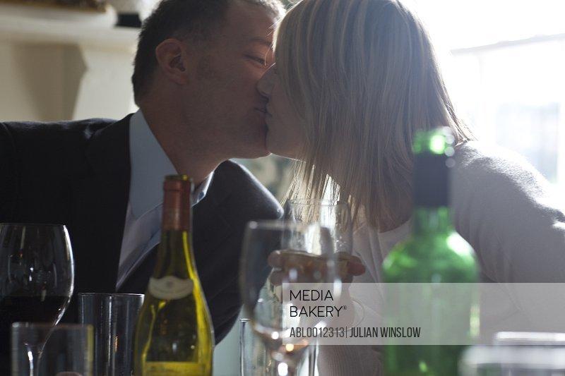 Couple sitting in restaurant kissing