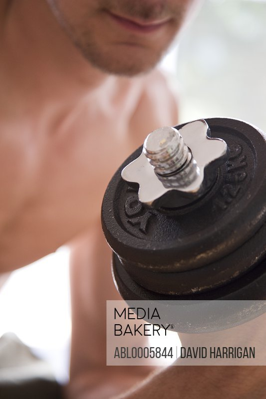 Close up of young man lifting dumbbell