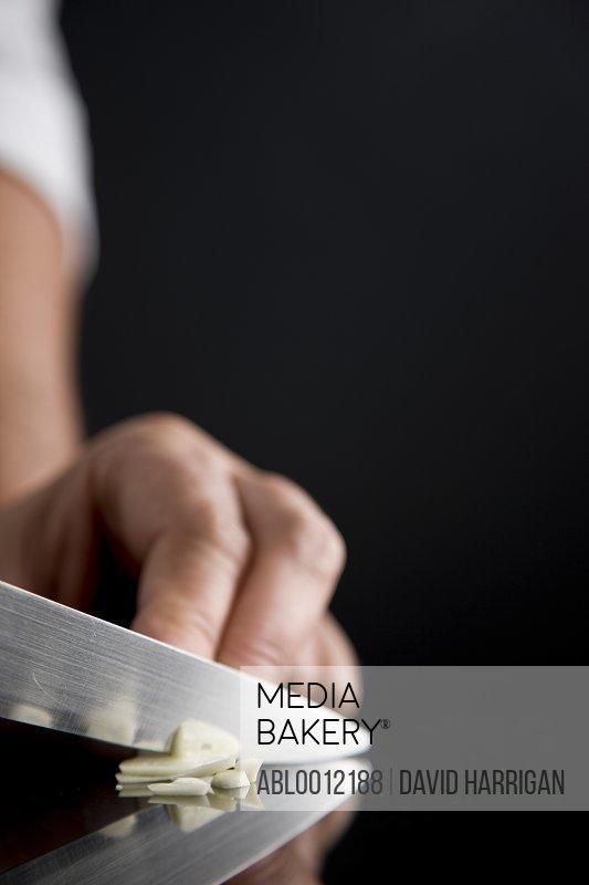 Close up of a chef hand slicing garlic