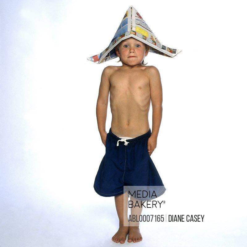 Boy Wearing Newspaper Hat Standing Straight and Stiff