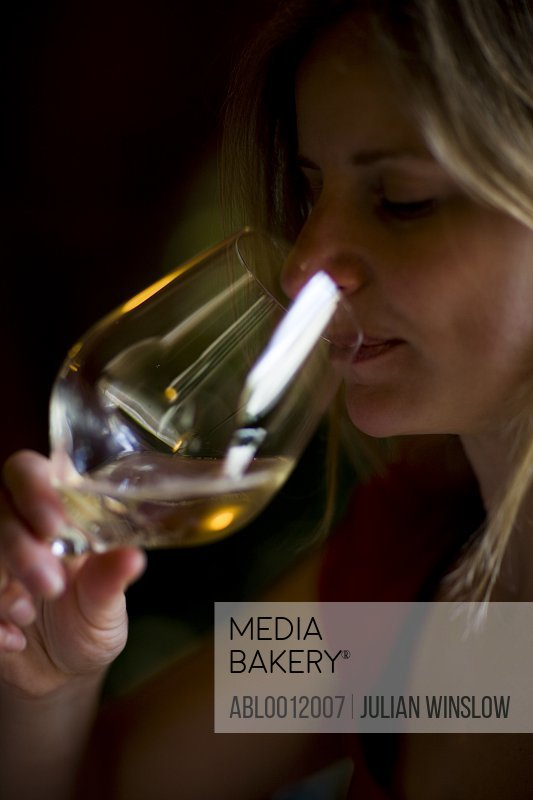 Close up of a woman holding a glass and tasting white wine
