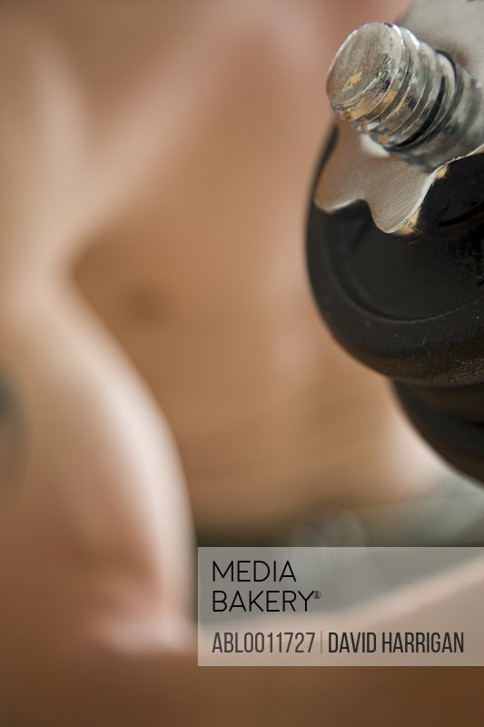 Close up of young man arm lifting dumbbell