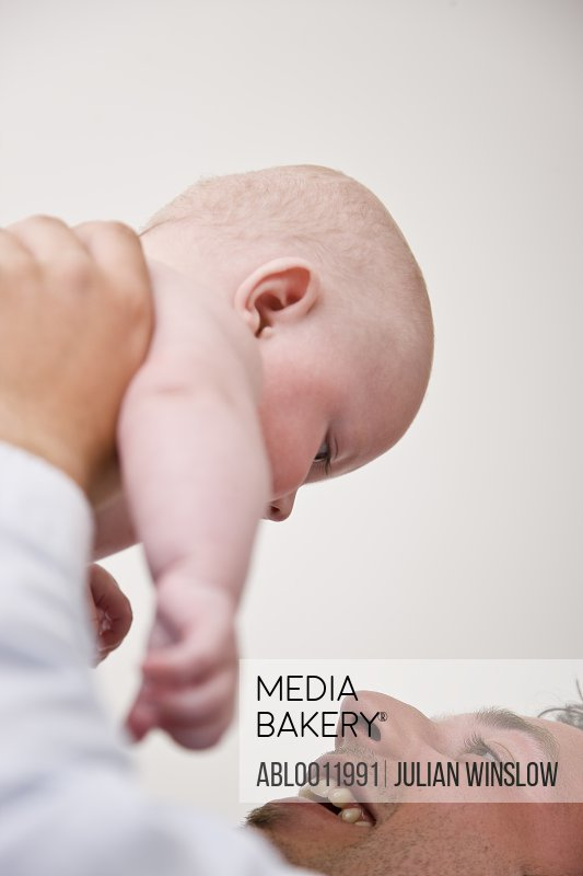 Man lifting baby over his head smiling