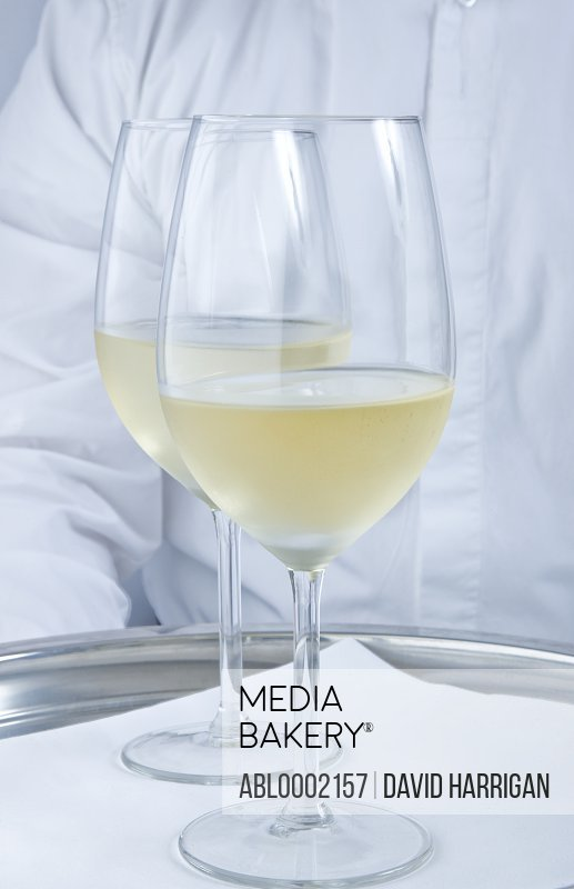 Waiter Holding Tray with Glasses of White Wine - Close-up view