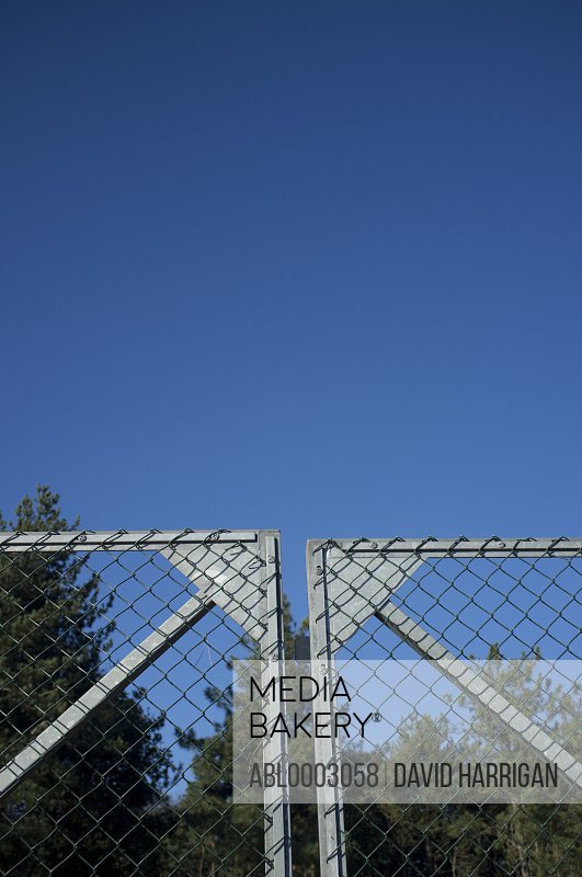 Closed Metal Gate against Blue Sky