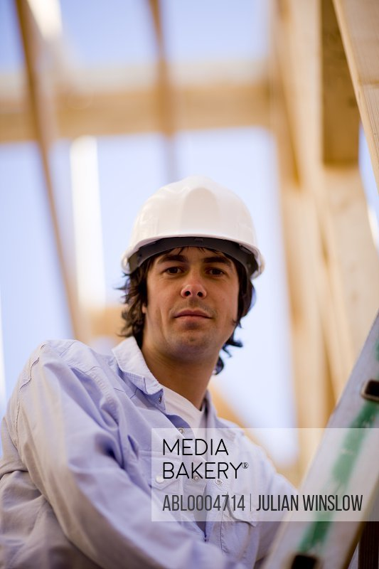 Close up of a young man climbing a ladder at construction site