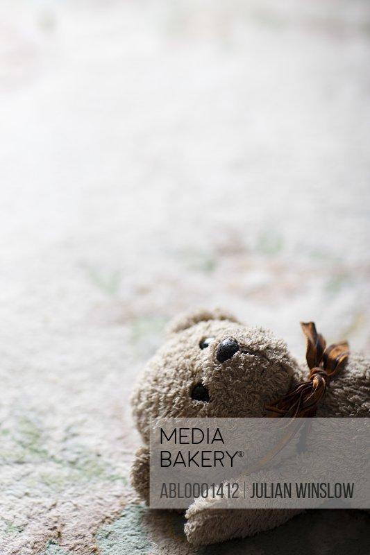 Close up of a teddy bear lying on a carpet