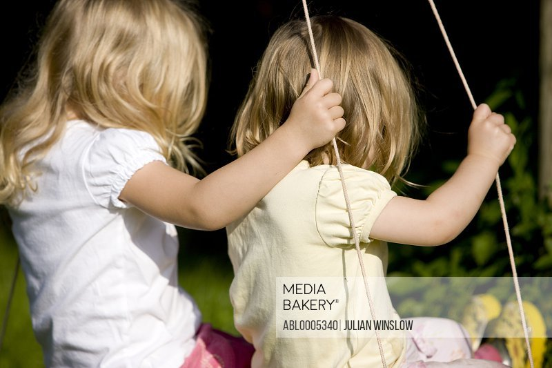 Back view of two young girls on swing