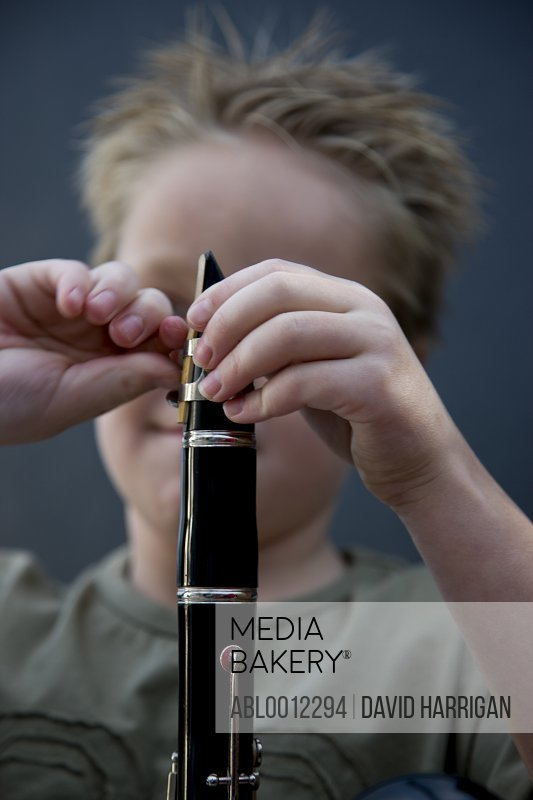 Close up of a boy hands putting together a clarinet