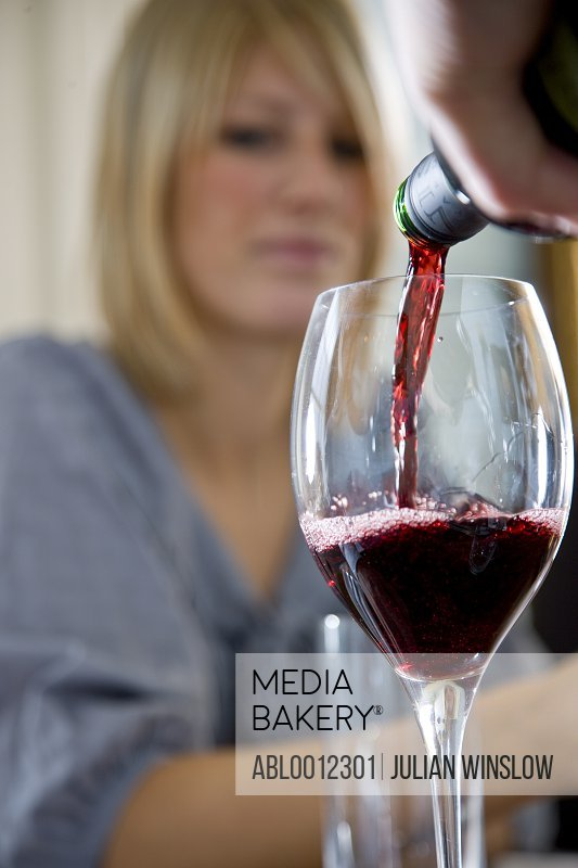 Close up of a hand pouring red wine into a glass with woman behind