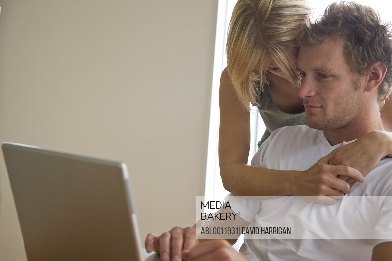 Young couple in front of laptop computer  embracing