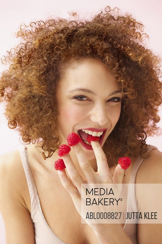 Smiling Young Woman Biting and Wearing Raspberries on Fingertips