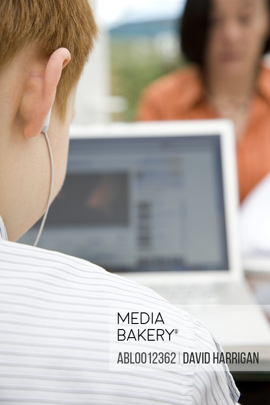 Back view of a boy using a laptop and wearing earphones sitting opposite woman