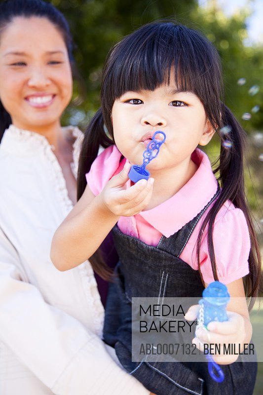Girl Blowing Soap Bubbles in her Mother Arms