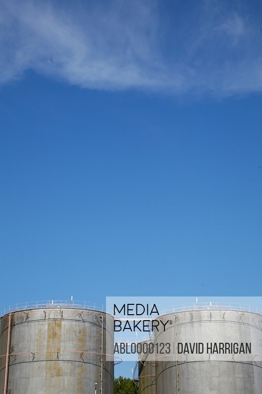 Industrial storage tanks against blue sky