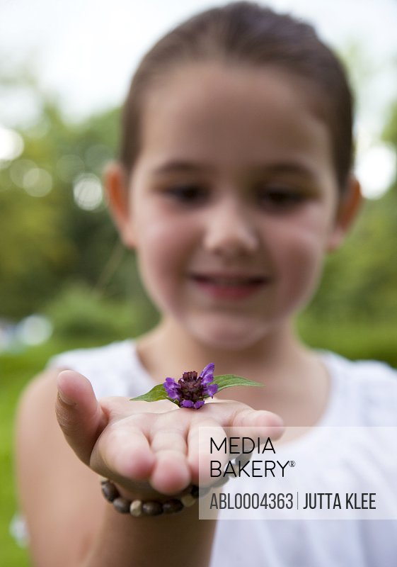 Young girl holding purple flower on her hand