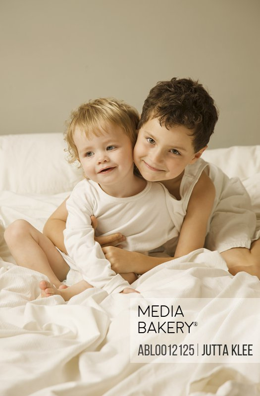 Young boy and toddler sitting in bed hugging and smiling