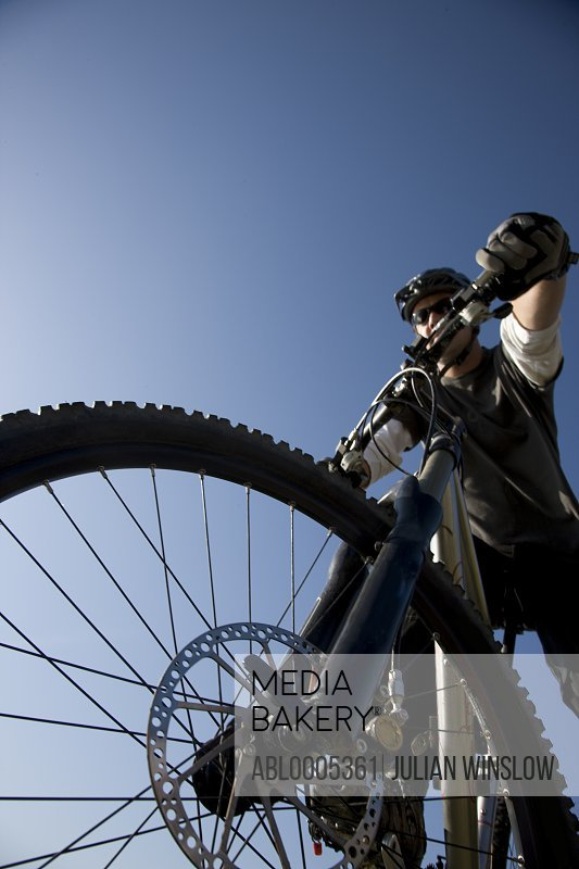 Man on a bicycle against blue sky