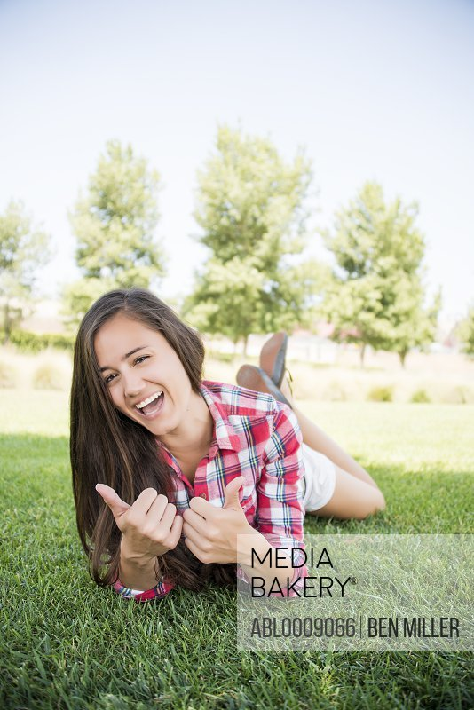 Woman Lying on Grass Giving Thumbs Up