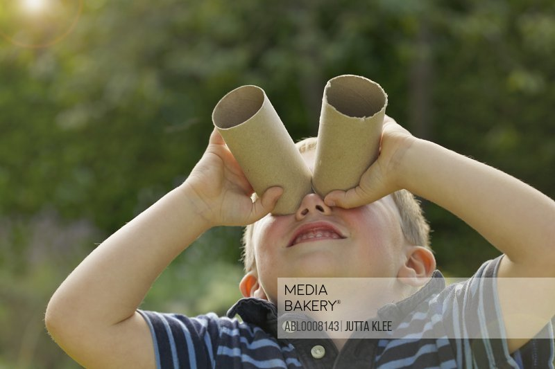 Young Boy Looking Through Empty Toilet Paper Rolls