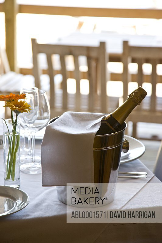 Unopened champagne bottle in an ice bucket on a restaurant table